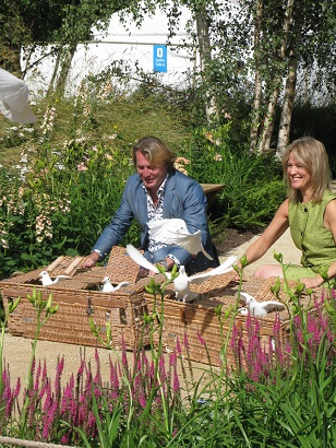 David Domoney and helper releasing doves at The Quiet Mark Tree House, Hampton Court Flower Show 2014